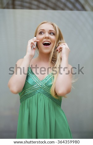 Young beautiful blonde woman in the green dress talking on cell phone, indoor