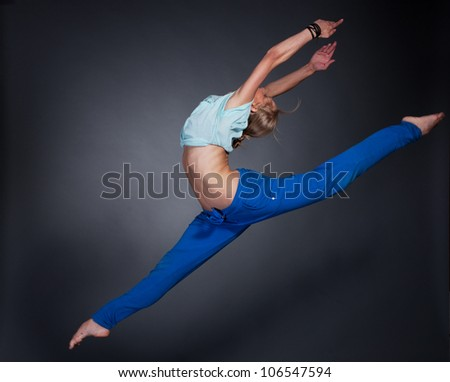 young beautiful blonde woman jumping in the splits - stock photo