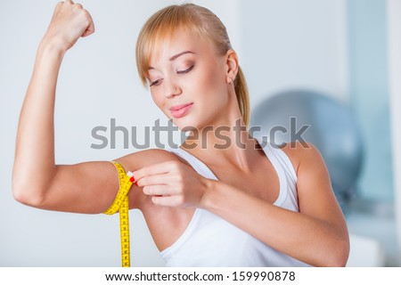 young beautiful blonde woman measuring her biceps with tape - stock photo