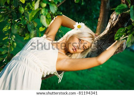 Young beautiful blonde woman near apple tree