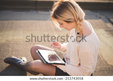 young beautiful blonde woman outdoor in the street of the city using technological device tablet connected online wireless sitting in the ground - stock photo