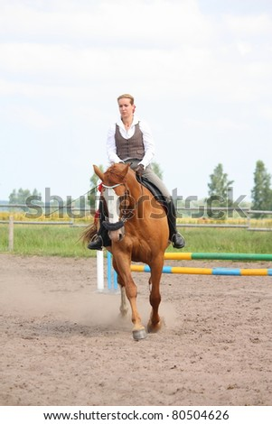 Young beautiful blonde woman riding on chestnut danish warmblood horse