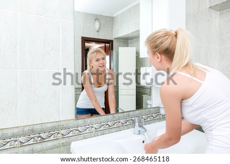 Young beautiful blonde woman washing face and hands - stock photo