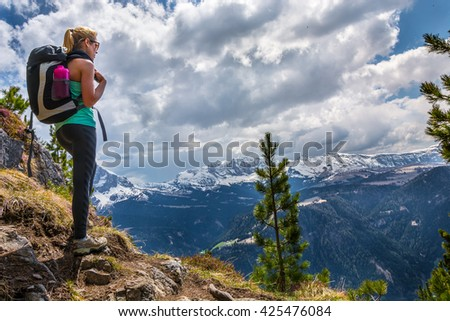 Young beautiful blonde woman watching the landscape near the top of Monte Pic in Italy