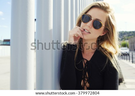 Young beautiful blonde woman wearing fashionable sunglasses while posing outdoors in sunny spring day,charming hipster girl looking at camera while standing in the fresh air during her walking outside - stock photo