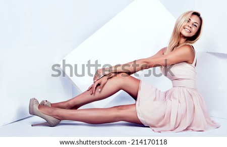 Young beautiful blonde woman with long slim legs posing, wearing fashionable dress, looking at camera - stock photo