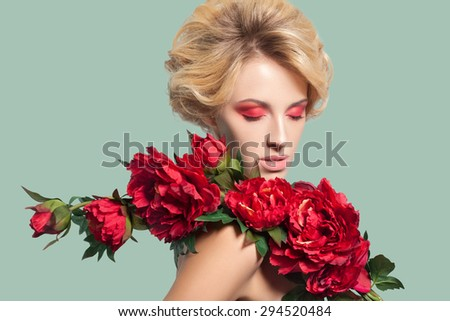 young beautiful blonde woman with red makeup and flowers on green background. studio shot. closed eyes. Developed from RAW, edited with special care and attention - stock photo