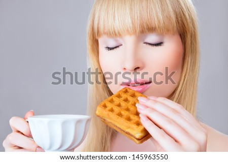 Young beautiful blonde woman with tea cup against light gray background - stock photo