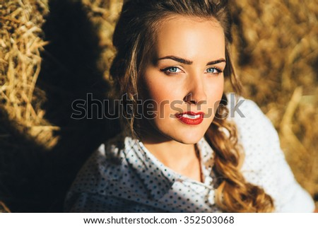 Young beautiful blue-eyed blonde in shirt on straw background. country style