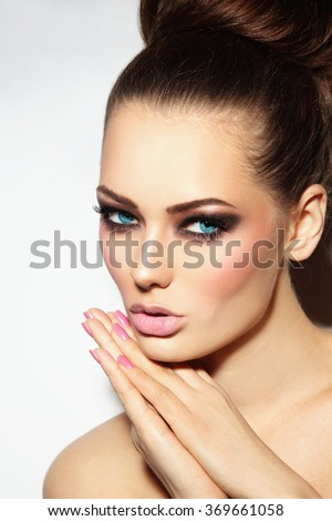 Young beautiful blue-eyed woman with smoky eyes and hair bun - stock photo
