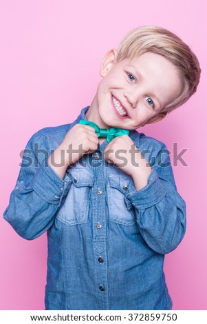 Young beautiful boy with blue shirt and butterfly tie. Studio portrait over pink background - stock photo
