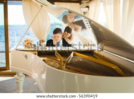 Young beautiful bride and groom at the white grand piano on a boat with a river at the background - stock photo