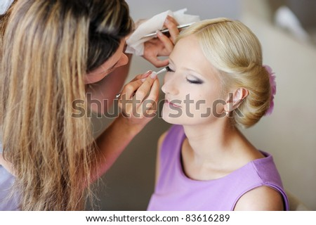 Young beautiful bride applying wedding make-up by make-up artist - stock photo