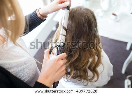 Young beautiful bride applying wedding makeup by professional makeup artist