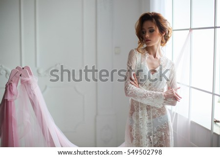young beautiful bride dressed before the wedding ceremony standing near the window all white
