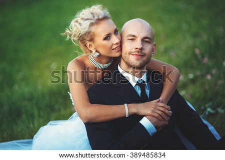 young beautiful bride gently embraces the groom in a suit sitting on the lawn in summer