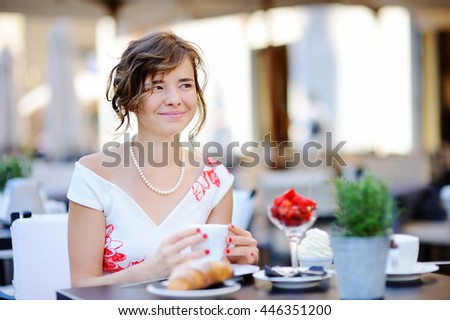 Young beautiful bride having breakfast with coffee and berries at the outdoors cafe during her wedding day