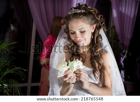young beautiful bride hold white flowers in restaurant - stock photo