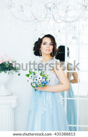 Young beautiful bride in wedding dress colors of serenity. Antique white interior. Wedding bouquet in hands.