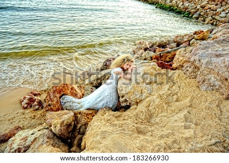 Young beautiful bride leaning on the rock at the beach and daydreaming. Romantic moment by the ocean.  - stock photo