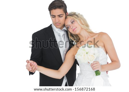 Young beautiful bride posing with her husband holding a white bouquet - stock photo