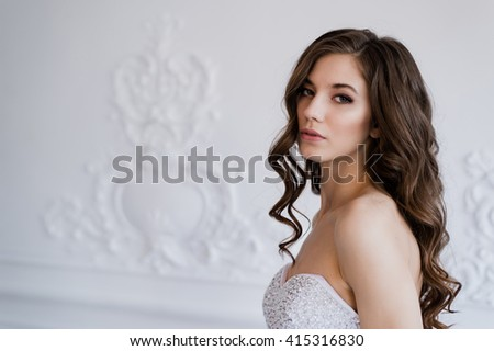 Young beautiful bride standing in antique interior ornamental design done with a moldings. Studio shot - stock photo