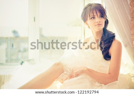 Young beautiful bride waits for groom near the window - stock photo