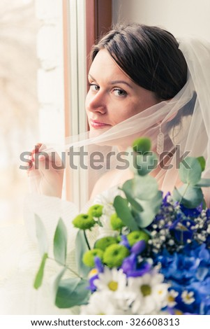 Young beautiful bride waits for groom near the window