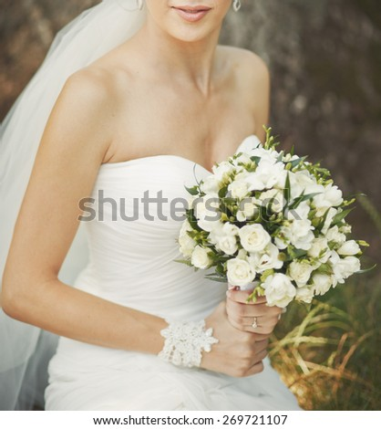 Young beautiful bride with bouquet in hands.