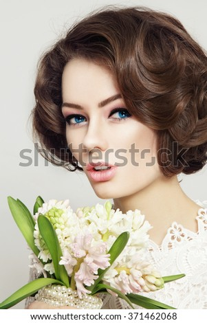 Young beautiful bride with stylish make-up and hairdo holding bouquet  - stock photo