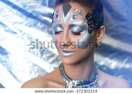 Young beautiful, bright, showy girl, lady, model, dancer,queen. Fairy tale, future, party, disco, techno, club. Art makeup, flawless face, silver eyes, cheeks, eyebrows, lips. Forehead is adorned gems - stock photo