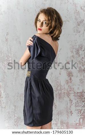 Young beautiful brown-haired woman in a blue dress with bare shoulders and backs against the wall and worth looking dreamily