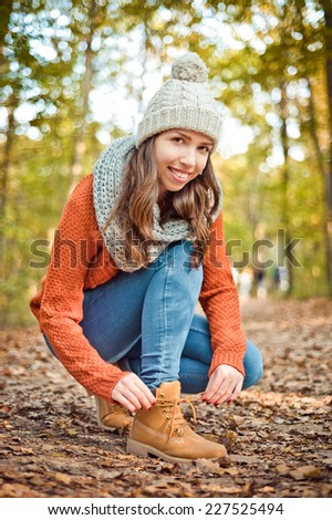 Young beautiful brown hiker girl in orange sweater and knitted hat tie the shoelace of her yellow boots in the cold autumn forest and enjoy the last warm hours - stock photo