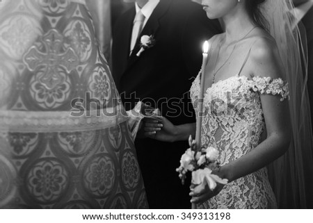 Young beautiful brunette bride and handsome groom holding candle with priest b&w - stock photo