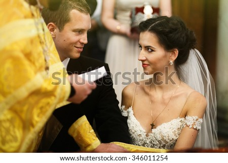Young beautiful brunette bride and handsome groom with priest taking vows - stock photo