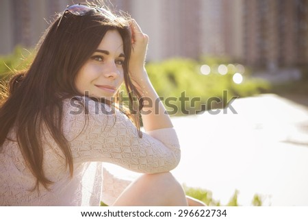 Young beautiful brunette caucasian girl in white dress sitting on a grass with her back to us, looking at us. summer day, outdoors. lifestyle. leisure. copy space - stock photo