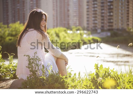 Young beautiful brunette caucasian girl in white dress sitting on a grass with her back to us, looking in front of her. summer day, outdoors. lifestyle. leisure. copy space