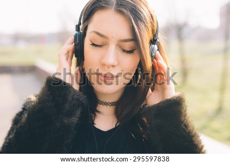Young beautiful brunette caucasian girl listening to the music with headphones in a city park - music, relax, serenity concept