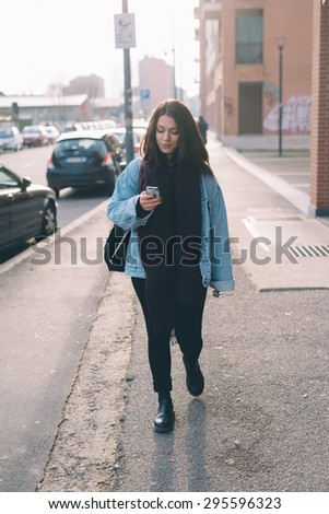 Young beautiful brunette caucasian girl walking down the street while using her smartphone - technology, internet, social network concepts