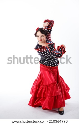 young beautiful brunette female spanish flamenco dancer in black blouse and red flamenco skirt dancing with her hands in studio on gray background - stock photo