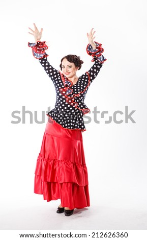 young beautiful brunette female spanish flamenco dancer in black shirt and red flamenco skirt posing with red fan in her arms in studio on gray background - stock photo