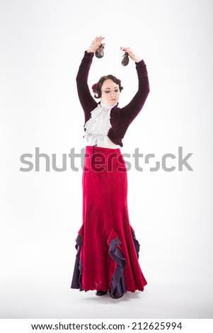young beautiful brunette female spanish flamenco dancer in white blouse and red flamenco skirt dancing with castanets her hands in studio on gray background - stock photo