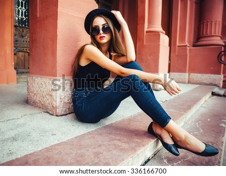 young beautiful brunette girl in a hat, sunglasses, t-shirt and jeans, walking on the ancient city