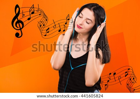 Young beautiful brunette girl, in black blouse, listening to music with big blue headphones on geometric orange background with musical notes - stock photo
