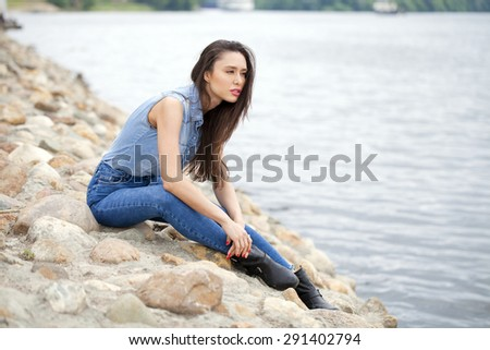 Young beautiful brunette girl in blue jeans sitting on the rocks on the river bank
