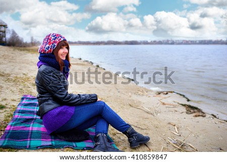 Young beautiful brunette girl in blue jeans sitting on the sand by the river