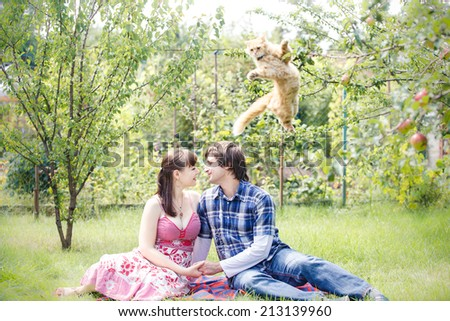 young beautiful brunette girl in pink dress with her handsome man in blue shirt sit in green garden - stock photo