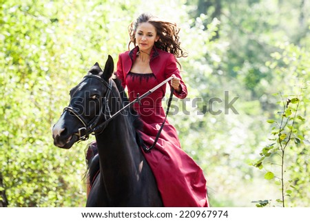 young beautiful brunette girl in red dress ride on the black horse in green forest