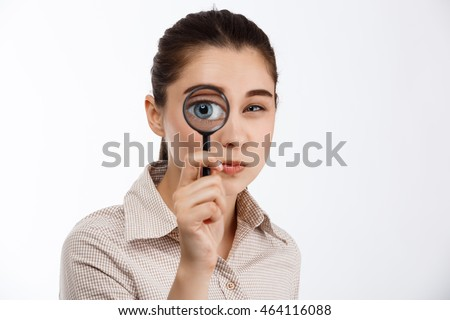 Young beautiful brunette girl looking with mistrust at camera through magnifier over white background.