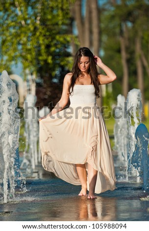 young beautiful brunette girl playing at outdoor water fountain - stock photo